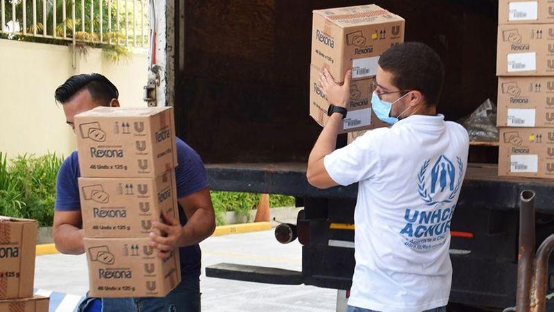 UNHCR representatives unloading boxes full of Unilever's Rexona at a refugee camp