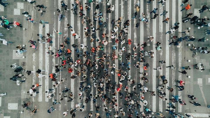 Aerial view photograph of a large number of people crossing a road.