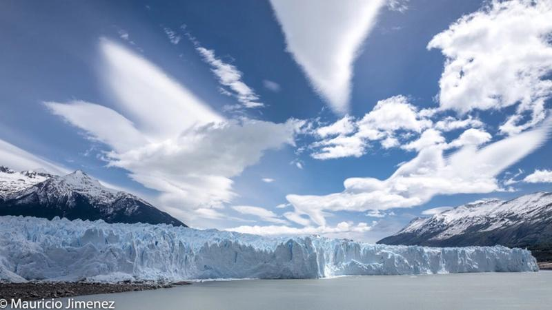 View of the terminus of a glacier as seen from sea level with mountains in the background and a bright, sunny sky