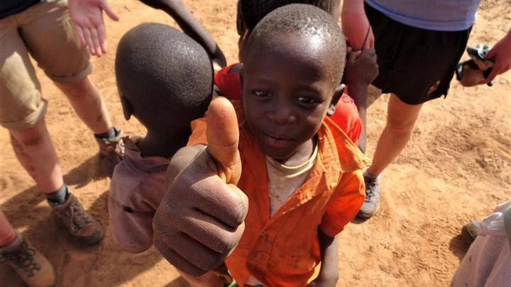 A young boy with his thumb up
