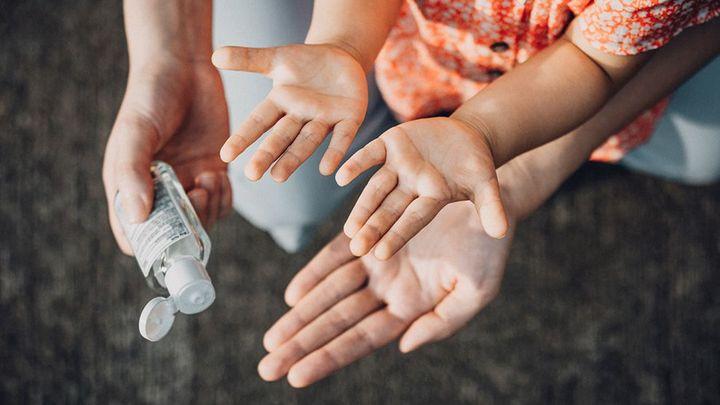 Hands applying hand sanitiser gel