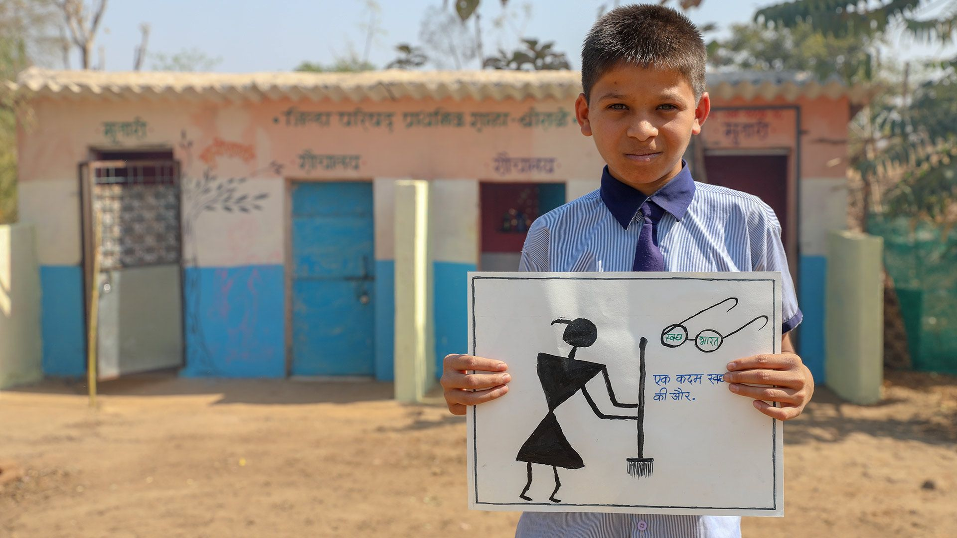 A young schoolboy outside a toilet in India holds up a poster about keeping toilets clean