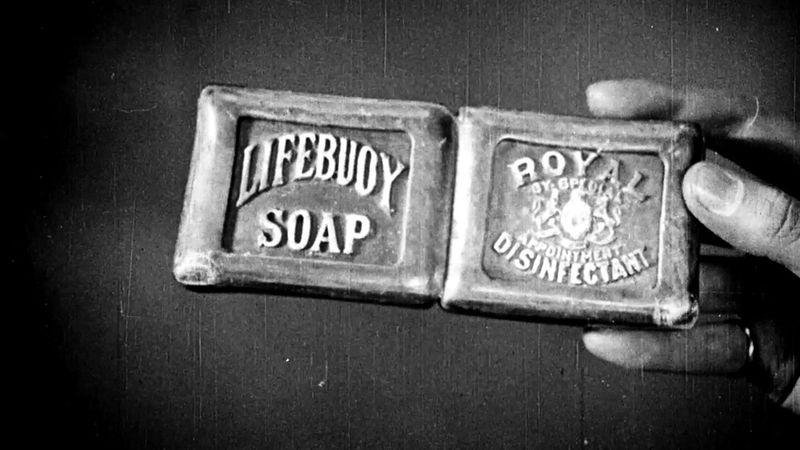 A black and white image of a hand holding an original Lifebuoy bar of soap