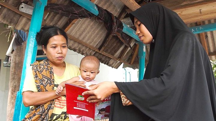 A young family reading a Knorr recipe book