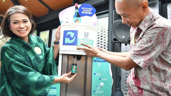 Man and woman refill bottle. Indonesian brand, Bango is one of 11 products on offer at Unilever's pilot refillery.