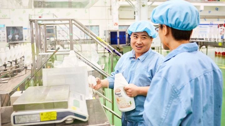 Two men in blue overalls talking to each other at our factory in China