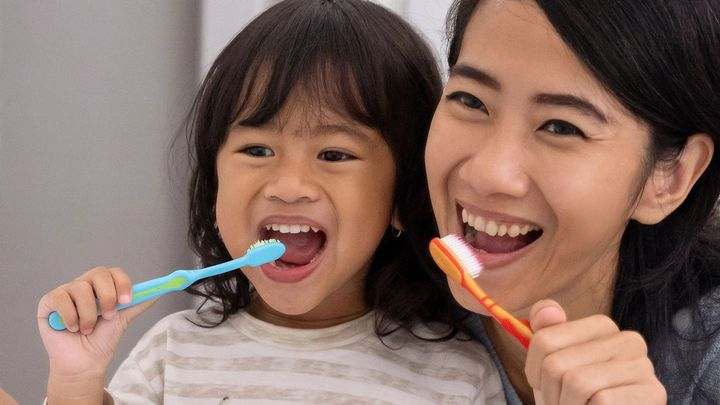 Mother and toddler daughter cleaning their teeth side by side at the bathroom sink