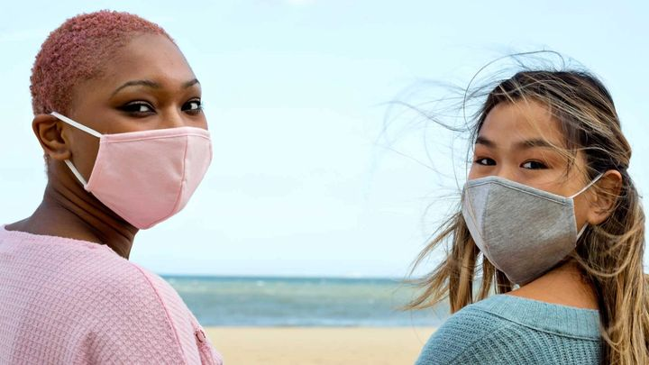 Two women wearing face masks on a beach