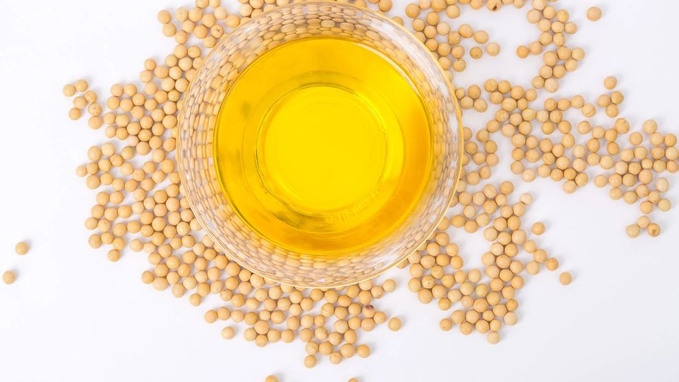 Top view of soybeans and a bowl of soybean oil