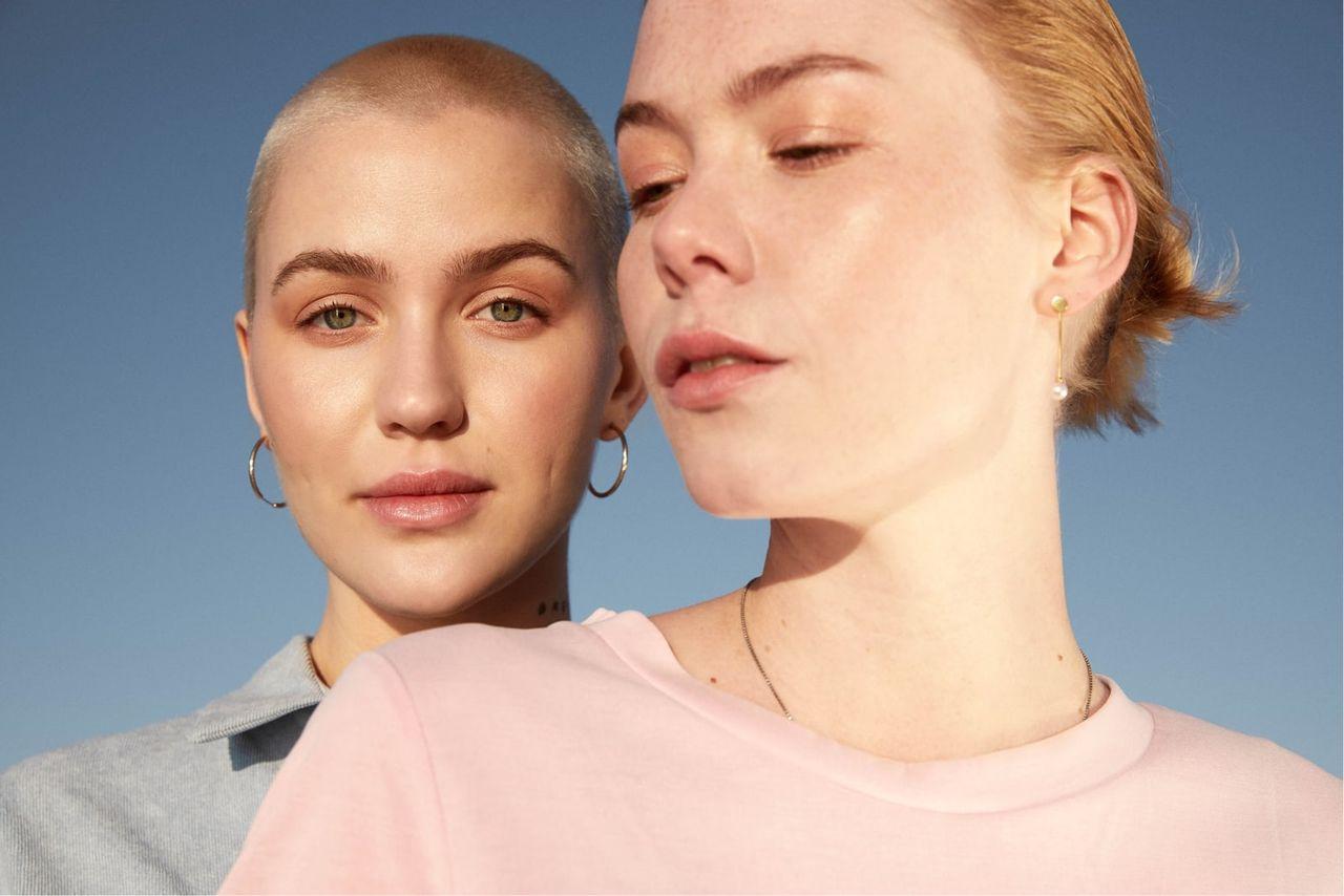 To jenter foran en blå himmel