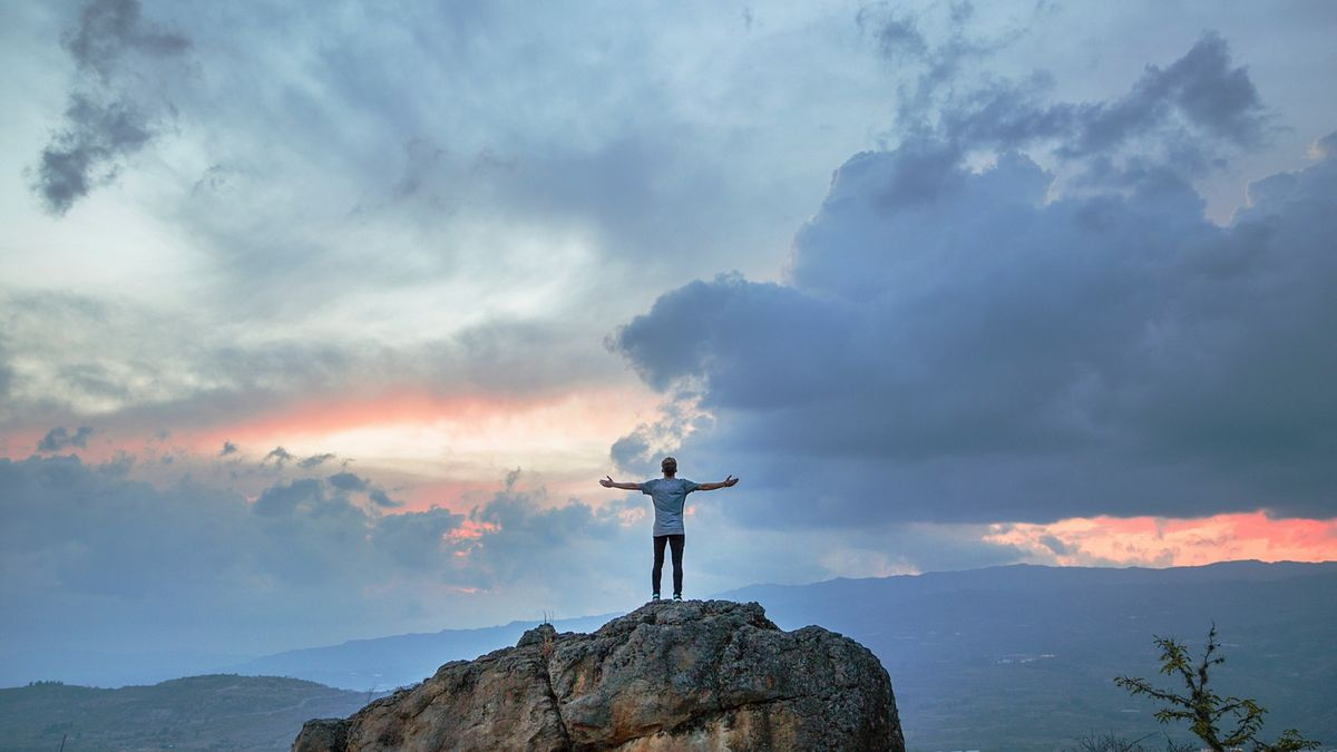 Joshua Earle's photo of the back of a man with arms out wide on top of a boulder that is overlooking a cloudy landscape with the sun setting.