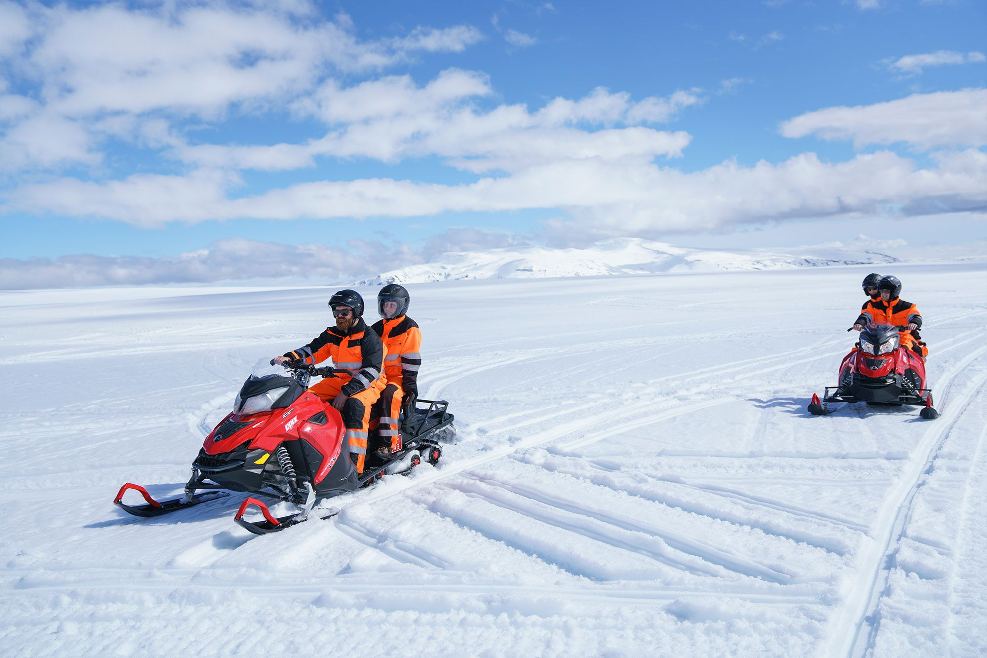 couples riding snowmobiles on langjökull glacier