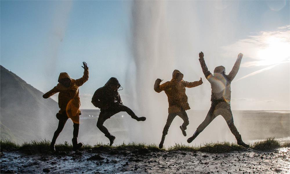 Travelers having fun behind Seljalandsfoss waterfall