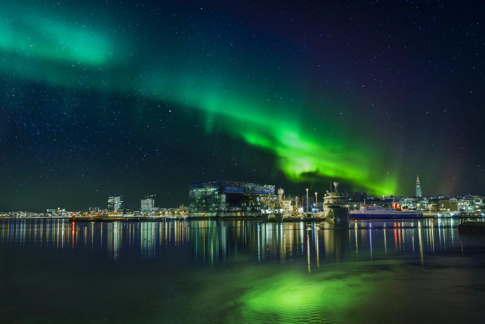 Aurora borealis over Hapra concert music hall in downtown Reykjavik