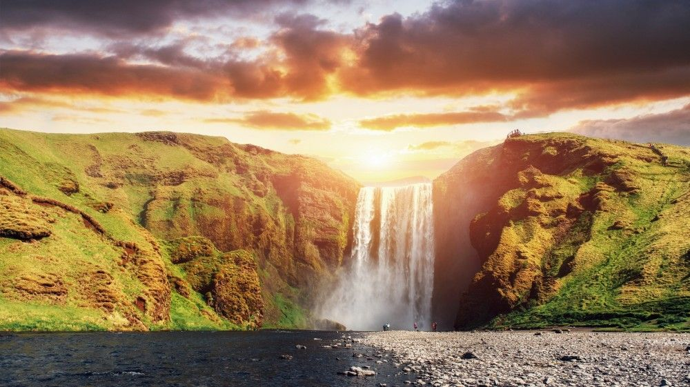 Midnight sun over the Skógafoss waterfall in Iceland