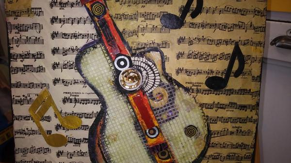 mixed media of acoustic guitar with music sheets