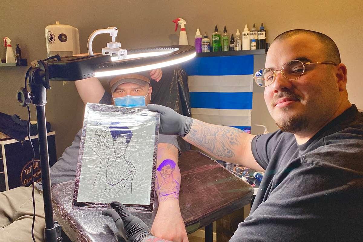 Maury (25) synar fram tatoveringa som kunden, Mathew, sjølv har teikna. (Foto: Ørjan Håland)