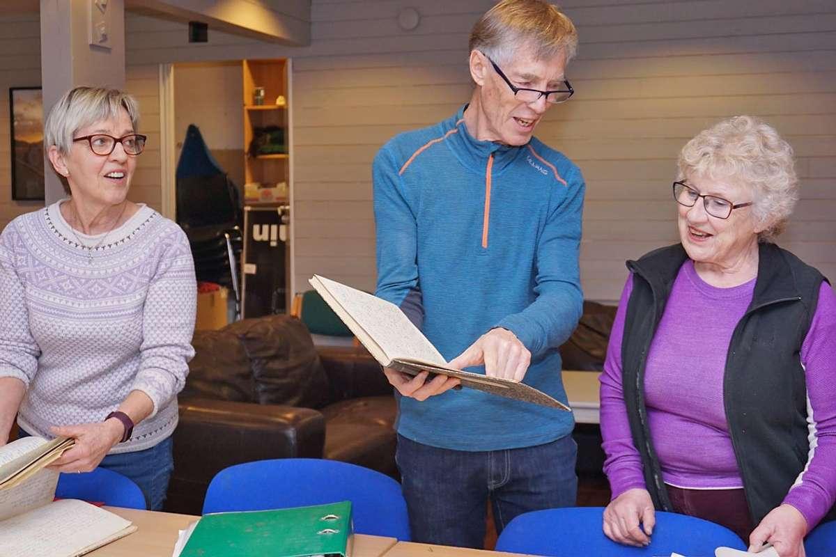 F.v.: Brit Eirin, Tore og Grethe tar seg tid til å bla litt i gamle bøker, sjølv om ryddejobben er stor.
