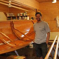 Maik Riebort framfor båten han snart er ferdig med (Foto: KMAL)