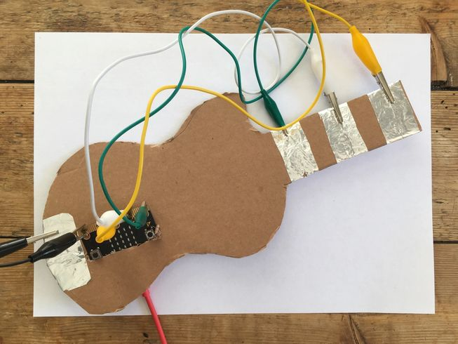 photo showing tin foil pads wired up to micro:bit pin 0, 1, 2 and GND on a cardboard guitar