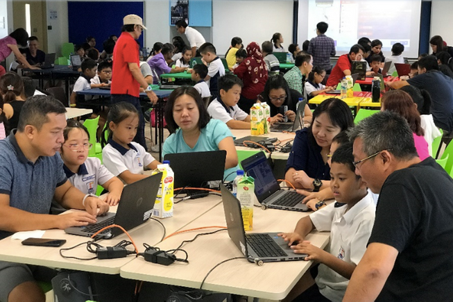Parents and children working on laptops together