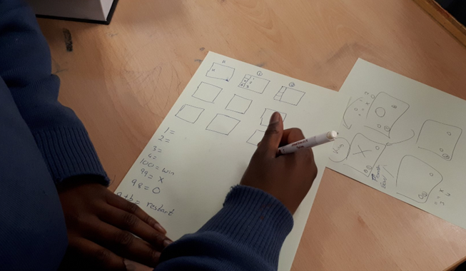A student drawing a coding activity on paper