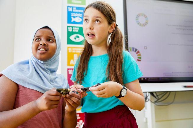 两位年轻的女孩对 micro:bit 感到惊奇