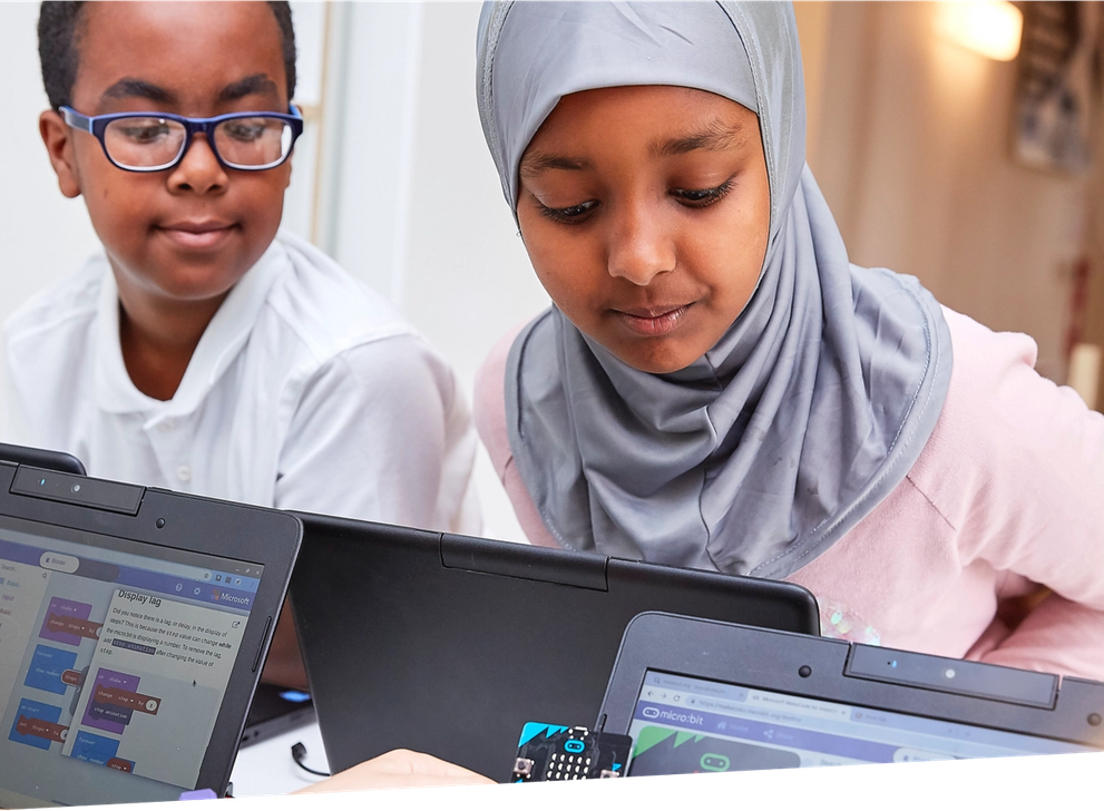 Crianças na aula a programar micro:bits no editor MakeCode