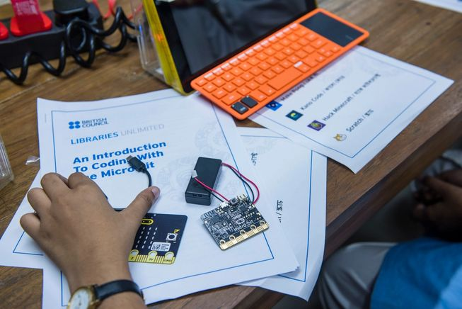 A students hands at desk with micro:bits and laptop