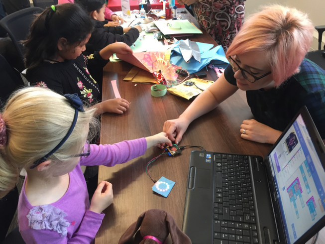 A teacher working with micro:bits with two young students