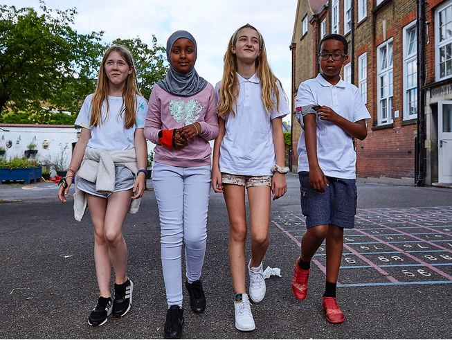 Four children wearing micro:bit step counters and activity monitors