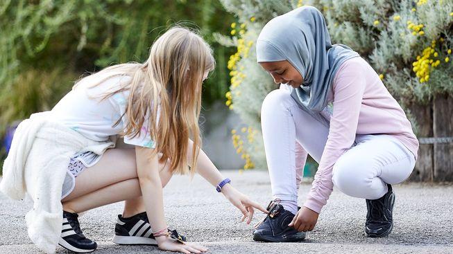 女孩指着另一个女孩鞋子上的 micro:bit 计步器