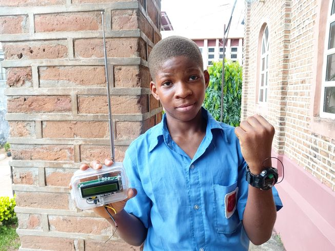 A boy holds up two parts of a tech device
