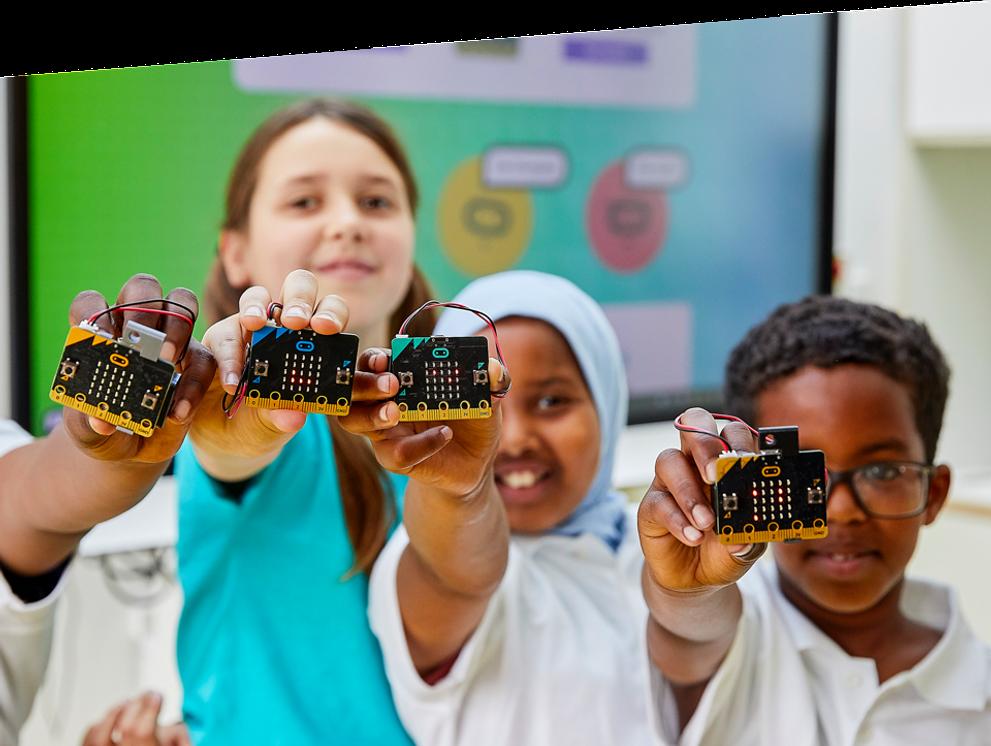 enfants en classe souriants et tenant en main des micro:bits