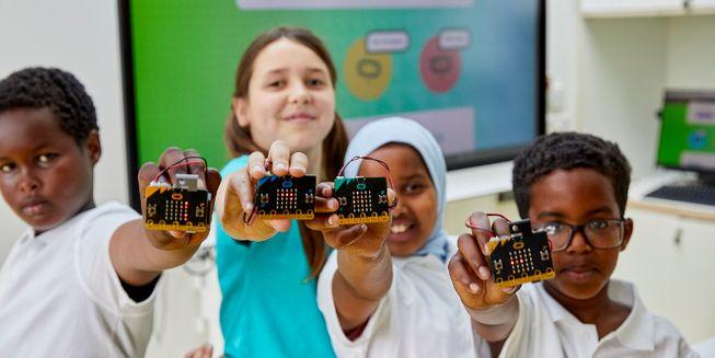 Primary school children holding micro:bits