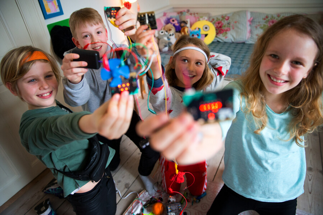Four children smiling holding up micro:bits