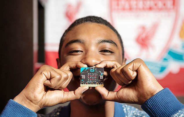 Boy holding micro:bit up to face