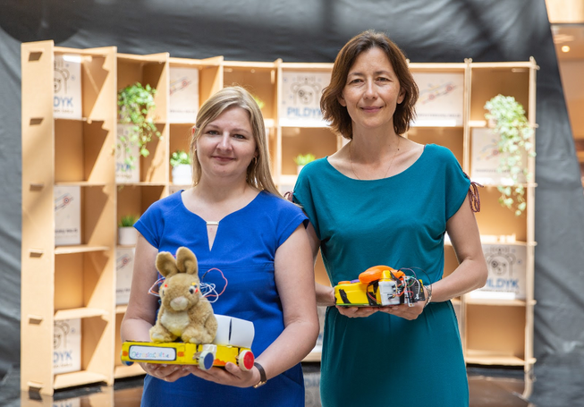 Two women standing together holding robot toys