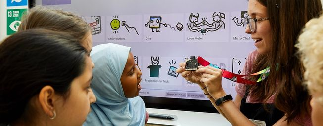 teacher showing micro:bit to children