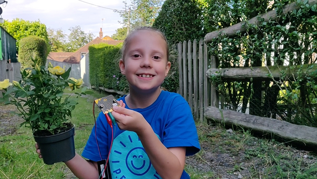 Child showing micro:bit plant moisture project in their garden