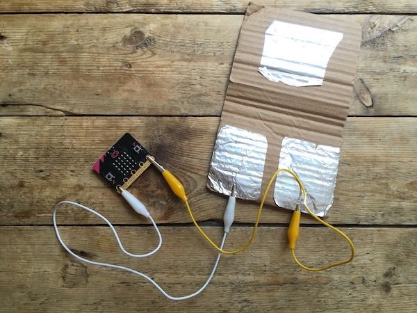 Sensor micro:bit with pin 0 connected to one foil pad, GND pin connected to another. A flap of cardboard with foil folds over and connects the two other foil pads when someone treads on it.