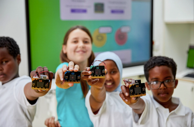 Four children holding up micro:bits