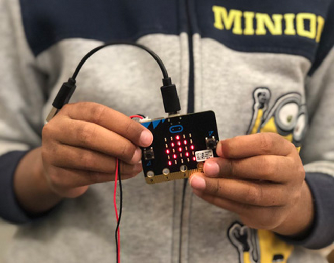 A boy holding up a micro:bit