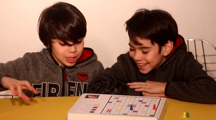 two boys playing a micro:bit Ludo game