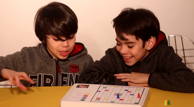 Two boys playing a board game with a micro:bit