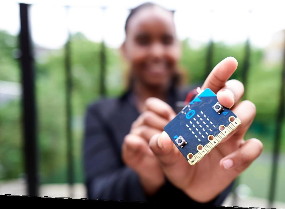 Uma aluna a mostrar um micro:bit
