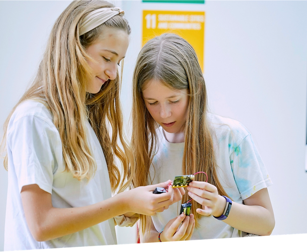 two girls examining a micro:bit