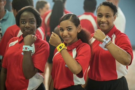 Three girls wearing micro:bit step counters