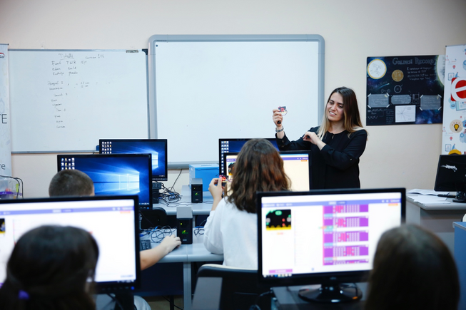 A teacher in front of a class holding up a micro:bit