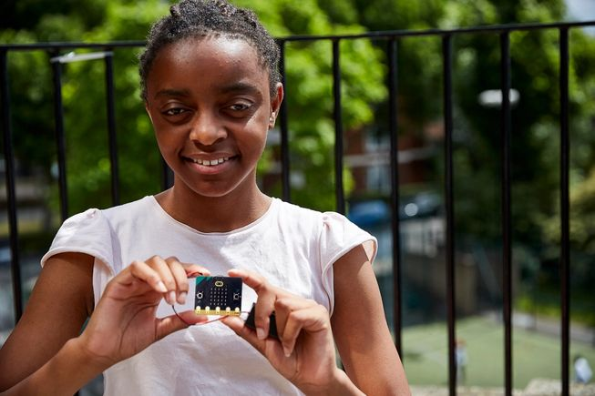 a young girl holding a new micro:bit
